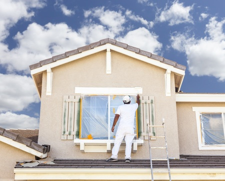 38716815 - busy house painter painting the trim and shutters of a home.